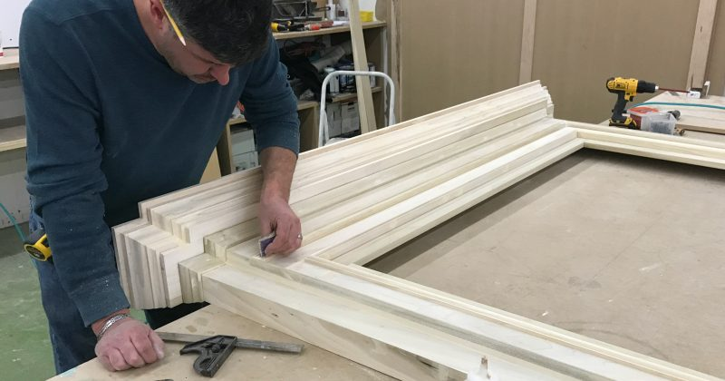 man creating a custom fireplace and Installing Wainscoting